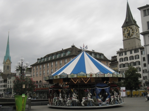 A cloudy day in Zurich. A temporary carousel in the middle of the city centre.
